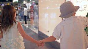 有包裹的顾客孩子在季节性销售期间是昂贵的精品店观察孔在购物中心的 股票录像