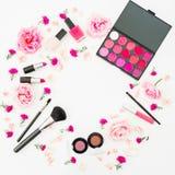有化妆和桃红色花的女性圆的书桌在白色背景 平的位置,顶视图 妇女的秀丽框架 图库摄影