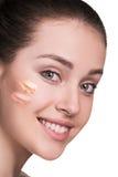 有化妆基础的妇女在皮肤 图库摄影
