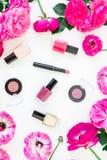 有化妆用品、唇膏、眼影、桃红色花指甲油和框架的秀丽书桌在白色背景的 平的位置,顶视图 图库摄影