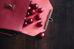 有化妆用品和成熟樱桃的时髦的提包 免版税库存照片