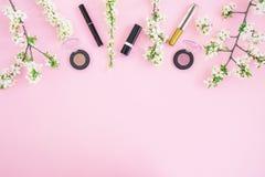 有化妆用品的女性书桌:唇膏、阴影、染睫毛油和白色春天在桃红色背景开花 平的位置,顶视图 秀丽co 图库摄影
