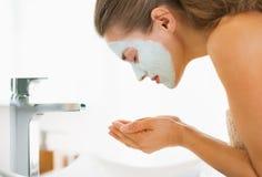 有化妆面具的少妇在面孔洗涤物 免版税库存图片