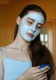 有化妆面具的少妇在他的拿着手奶油的面孔 免版税库存图片