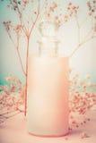 有化妆水或身体关心奶油的瓶与花,自然化妆产品或者秀丽概念在淡色背景 免版税库存照片