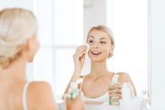 有化妆水洗涤的面孔的少妇在卫生间 免版税库存照片