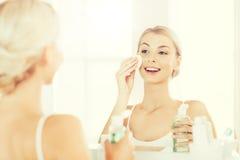 有化妆水洗涤的面孔的少妇在卫生间 库存照片