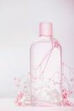 有化妆水的瓶、补剂或胶束纯净水、自然化妆产品或者秀丽概念在淡色背景 免版税库存图片