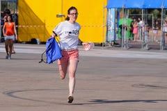 有北极泼猴带衬衣的,捉住第一行的奔跑一个女孩在小谎(Festival Internacional de Benicassim) 2013年节日 库存照片