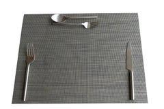 有匙子和刀子的板材席子在白色背景 库存图片