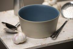 有匙子和大蒜的空的米黄平底的汤碗 库存照片