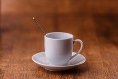 有匙子的一白色coffe杯在黑褐色木背景的白色茶碟 免版税库存图片