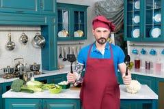 有匙子的勇敢的厨师在红色围裙和红色盖帽的手上 库存图片