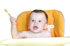 有匙子的可爱的婴孩在白色背景 免版税库存照片
