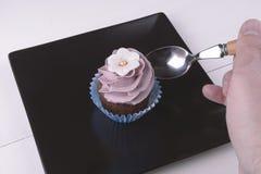 有匙子的手在杯形蛋糕 免版税库存图片
