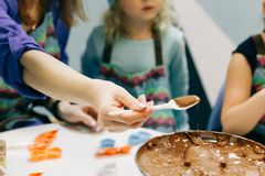 有匙子的手,从一把匙子的自创巧克力糖浆水滴到碗,在烹调巧克力的主要类里 免版税图库摄影