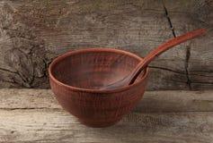 有匙子的空的黏土碗在木背景 图库摄影