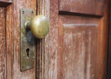 有匙孔的老门把在木门 库存照片