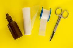 有医学绷带碘、卷,收口膏药和医疗剪刀的瓶在黄色背景 免版税库存图片
