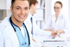 有医护人员的快乐的微笑的男性医生医院的 库存照片