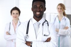 有医护人员的愉快的非裔美国人的男性医生医院的 免版税库存照片