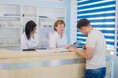 有医生和护士的男性患者总台的在医院 免版税图库摄影