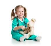 有医生衣裳的可爱的女孩有玩具的 免版税库存照片