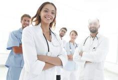 有医疗听诊器的可爱的女性医生在医疗小组前面 库存图片