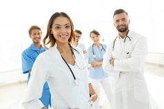 有医疗听诊器的可爱的女性医生在医疗小组前面 免版税库存图片