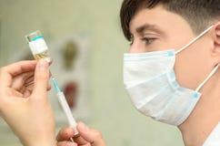 有医疗面具的男性美容师在面孔 免版税图库摄影