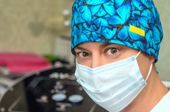 有医疗面具的男性美容师在面孔 免版税库存图片