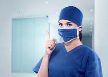 有医疗面具的美丽的亚裔护士指向她的手的 库存照片