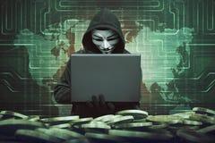 有匿名面具的戴头巾人使用对乱砍银行的膝上型计算机 免版税库存照片