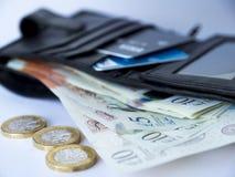 有十个和五磅笔记和1英镑硬币的钱包 免版税库存图片
