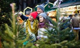 有十几岁的女儿的父母在X树市场上 浅深度o 免版税库存图片