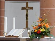 有十字架、蜡烛、花和圣经的法坛 免版税库存图片