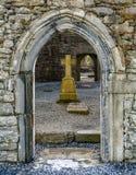 有十字架的在背景中, Corcomroe修道院,克莱尔郡,爱尔兰老石门户 免版税图库摄影