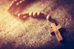 有十字架的木念珠在石背景 免版税库存图片
