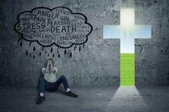 有十字架的标志的沮丧的人 免版税库存图片
