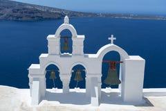 有十字架的白色教会和响铃在Oia,圣托里尼,希腊 图库摄影