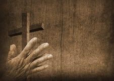 有十字架的祈祷的手 库存图片