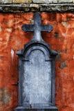 有十字架的老墓碑在粉碎的门面前面 库存图片