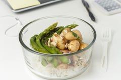 有午餐的一个玻璃容器在一张书桌上在工作 免版税库存图片
