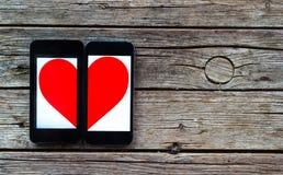 有半心脏标志的两个手机 免版税库存图片