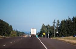 有半拖车的半卡车由平直的高速公路负责 免版税库存照片