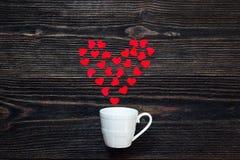 有华伦泰心脏的咖啡杯在黑暗的木桌上 Valen 免版税库存图片