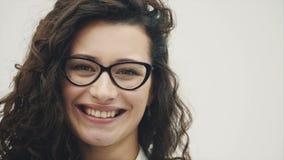 有华美的头发的年轻俏丽的女孩 在一个空白背景 恳切地穿戴在玻璃微笑 股票视频