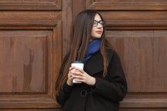 有华美的特长头发的年轻美丽的女孩在一条黑外套和蓝色围巾有一次性咖啡杯的获得乐趣反对wo 免版税库存照片