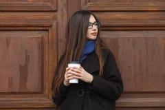 有华美的特长头发的年轻美丽的女孩在一条黑外套和蓝色围巾有一次性咖啡杯的获得乐趣反对wo 免版税库存图片