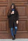 有华美的特长头发的年轻美丽的女孩在一条黑外套和蓝色围巾有一次性咖啡杯的获得乐趣反对wo 库存照片